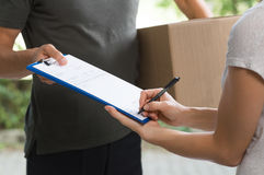 Woman signing delivery form stock photos