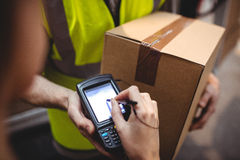 Woman signing on device to delivery parcel Stock Images