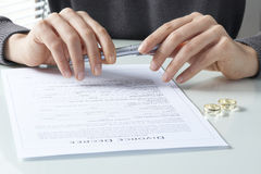 Woman signing divorce agreement with ring. Woman signing  divorce agreement with ring Royalty Free Stock Photography
