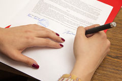 Woman signing a document Stock Image