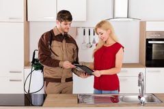 Woman Signing Document In Front Of Male Exterminator. Young Smiling Woman Signing Invoice From Exterminator Worker After Pest Control Work In House Kitchen Stock Photo