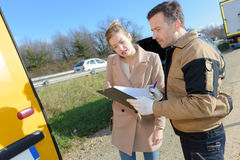 Woman signing insurance paperwork after car breakdown. Woman signing insurance paperwork after a car breakdown Stock Image