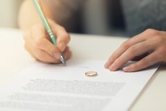Woman signing marriage divorce papers. On the table Royalty Free Stock Photos