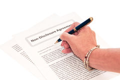 Woman Signing NDA Form. Non-Disclosure form to provide protection for industry secrets Royalty Free Stock Photo