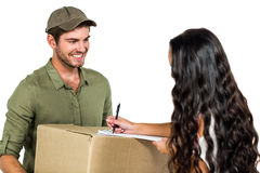 Woman signing for pack delivery with smiling postman Stock Image