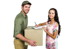 Woman signing for pack delivery with smiling postman Royalty Free Stock Photos