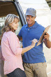 Woman Signing For Packager Delivered By Courier Stock Photography