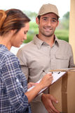 Woman signing for parcel. Woman signing for a courier delivered parcel royalty free stock image