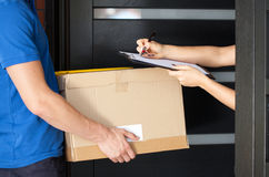 Woman signing parcel delivery papers Royalty Free Stock Photo