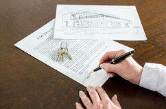 Woman signing a real estate contract. On a desk Stock Photo