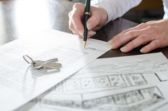 Woman signing a real estate contract. On a desk Stock Images