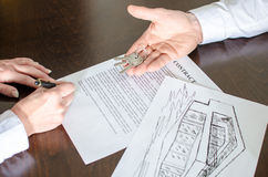 Woman signing a real estate contract. Realtor showing house keys and woman signing a real estate contract Royalty Free Stock Images