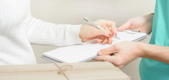Woman signing receipt of delivery package. Stock Image