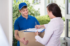 Woman Signing Receipt Of Delivery Package. Close-up Of A Woman Signing On Document Of Delivered Package Royalty Free Stock Images