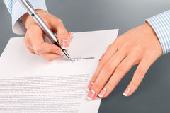 Woman signing rent contract. Royalty Free Stock Images