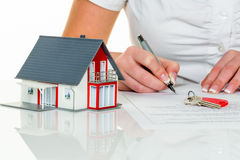 Woman signs agreement for house. A woman signs a purchase agreement for a house in a real estate agent Stock Photo