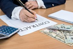 The woman signs the contract. dollar, calculator and pen. ÑŽ stock photo