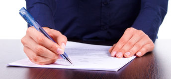 Woman signs a contract on a table, isolated over white Stock Images