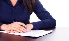 Woman signs a contract on a table, isolated over white Stock Image