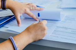 Woman signs a document Stock Photo