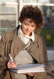 Woman signs documents. Young businesswoman signs the important documents stock photos