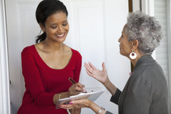 Woman signs a Petition. Black women signs a petition at her front door Royalty Free Stock Photos