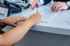 A woman signs a purchase document Stock Photography