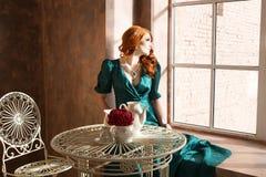 Woman siiting near window, vintage interior, luxury Stock Photo