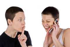 The woman silent and laughing friend with phon. The girl has brought a finger to lips and the laughing girlfriend has closed phone a hand Royalty Free Stock Photo