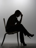Woman in silhouette. Sitting on chair Stock Photo
