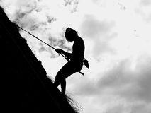 Woman silhouette. Rappeling down a rock Royalty Free Stock Photography