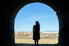 Woman silhouette on a ancient stone tunnel stock photo