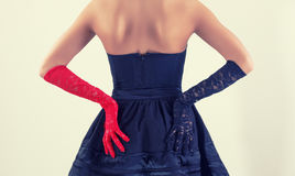 Woman silhouette from the back side in an elegant black dress. And colored lace gloves