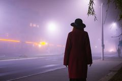 Woman silhouette on background of the night city in fog. Thick mist in dark scary evening city. Dark noir silhouette in hat on royalty free stock photos