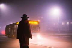 Woman silhouette on background of the night city in fog. Thick mist in dark scary evening city. Dark noir silhouette in hat on stock images