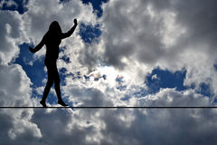 Woman silhouette balancing on rope Stock Photography
