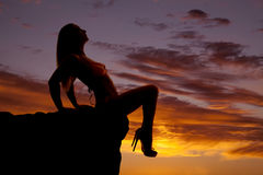 Woman silhouette bikini sit look up legs down. A woman in the sunset in a bikini sitting legs over edge royalty free stock photos