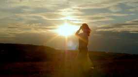 Woman silhouette dancing against sunset during sunset stock video footage