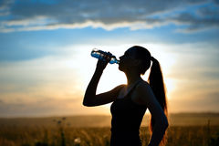 Woman silhouette drinking water Stock Photos