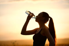 Woman silhouette drinking water Royalty Free Stock Images