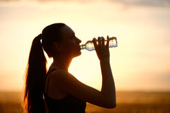 Woman silhouette drinking water Stock Images