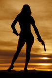 Woman silhouette with a gun down sunset Royalty Free Stock Image