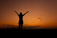 Woman silhouette with hands in the sky. Woman silhouette admiring the sunset sky Royalty Free Stock Image