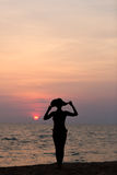 Woman silhouette with hat standing on sea background. Woman silhouette with hat standing on sunset sea background, side view, back lit stock photo