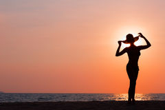 Woman silhouette with hat standing on sea background Stock Photos