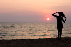 Woman silhouette with hat standing on sea background Royalty Free Stock Image