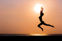 Woman silhouette jumping on sea background. Woman silhouette jumping on sunset sea background, side view, back lit Stock Photography