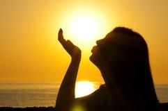 Woman silhouette kiss sun. A beautiful girl silhouette are kissing sun on the sea stock photos
