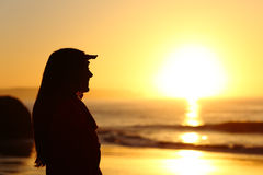 Woman silhouette looking forward at sunset Stock Images