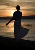 Woman silhouette next to the lake, sunset. Young woman with long skirt near to the lake Stock Photography
